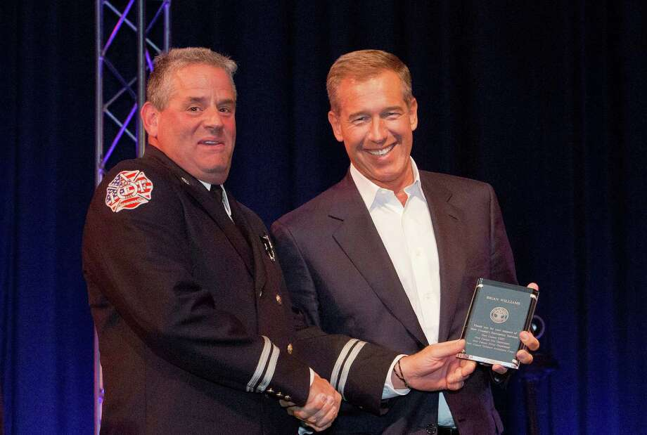 New Canaan Fire Company No. 1 Capt. Mike Socci receives an award on behalf of the department from Brian Williams, anchor and managing editor of NBC Nightly News, during a benefit concert Sunday, Sept. 30, 2013, honoring first responders. The event, held at New Canaan High School, included performances from residents Harry Connick Jr. and Paul Simon, and raised money for Staying Put in New Canaan. Photo: Contributed Photo / New Canaan News