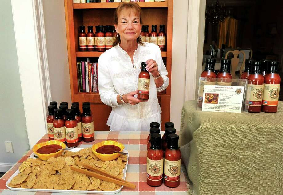 Pamela Ahtchi holds a bottle from her new condiment line, called Saha Sauces, in her Newtown, Conn., kitchen Monday, Sept. 30, 2013. Photo: Michael Duffy / The News-Times