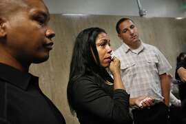 Lakesha James (center), daughter of Jill May, wipes a tear from her face as she answers a reporter's questions while standing with her husband Gary James (left) and brother Ricky James Jr. (right) outside of Department 24 at the Hall of Justice on Monday, September 30, 2013 in San Francisco, Calif.