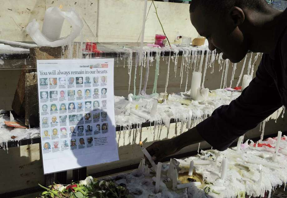On Monday, a Kenyan man lights a candle next to a list of the victims who were killed in the Westgate Mall massacre in Nairobi. Photo: Simon Maina / AFP / Getty Images