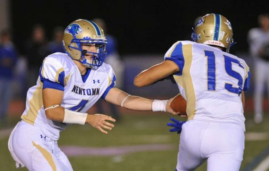 Newtown QB Andrew Tarantino , left, hands off to Julian Dunn during Friday's win at Brookfield. Photo: Tyler Sizemore