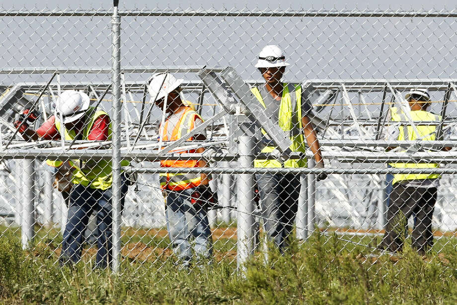 Workers build supports for dual-axis solar panels being installed at Alamo 1, a solar farm on South Blue Wing Road. Photo: Marvin Pfeiffer / Southside Reporter