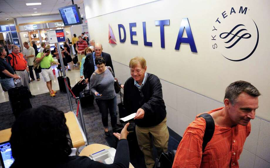 In this Friday, Sept. 27, 2013, photo, Delta Air Lines passengers, who have purchased an upgrade to board their flight early, take advantage of priority boarding as they make their way to their flight at Hartsfield-Jackson Atlanta International Airport in Atlanta.  Airlines are introducing a new bevy of fees, but this time passengers might actually like them. Unlike the first generation of charges which dinged fliers for once-free services like checking a bag, these new fees promise a taste of the good life, or at least a more civil flight. In the near future, airlines plan to go one step further, using massive amounts of personal data to customize new offers for each flier.  (AP Photo/John Amis) ORG XMIT: NYBZ403 Photo: John Amis / SPECIAL