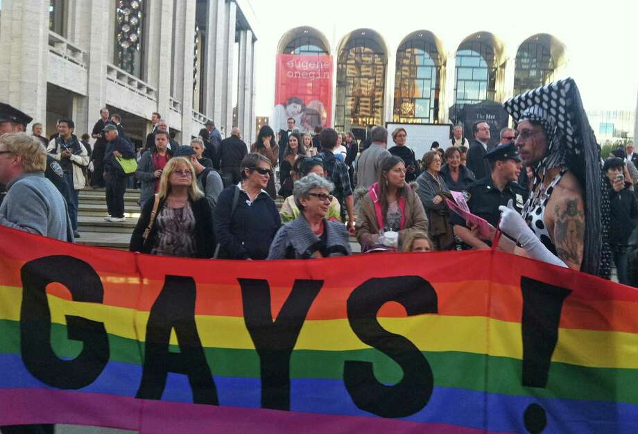 In this photo provided by Queer Nation NY, anti-Putin protestors demonstrate in front of the Metropolitan Opera at Lincoln Center, Monday, Sept. 23, 2013, in New York, where the Met held it's season-opening gala featuring soprano Anna Netrebko and conductor Valery Gergiev, two longtime supporters of  Russian President Vladimir Putin.  Putin, who has upheld anti-gay laws passed by the Russian legislature, has denied that homosexuals face discrimination in Russia and said the law does not infringe on their rights. Photo: Scott Wooledge, Queer Nation NY