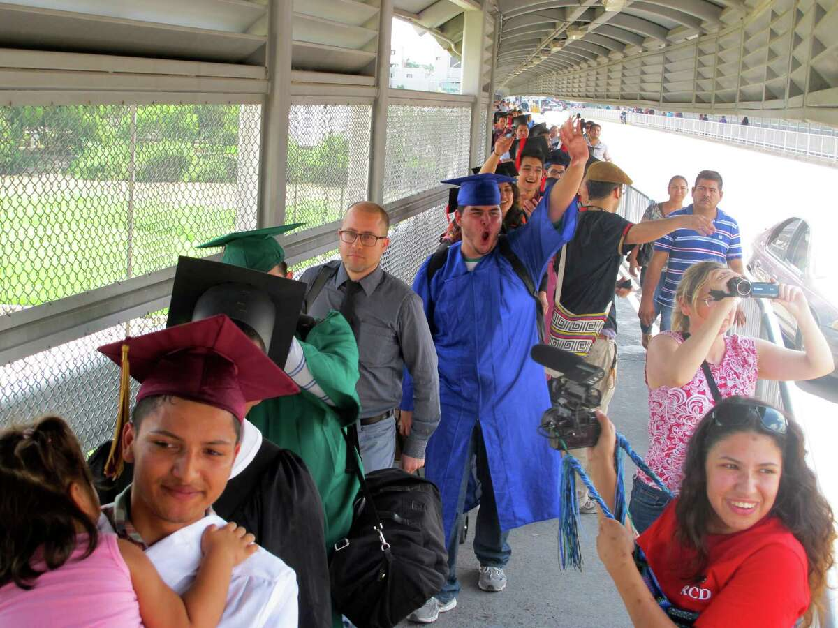 Wearing graduation-style cap and gown, U.S.-raised immigrant Alberto Peniche, 20, born in Mexico City and raised in Boston, waves and shouts as he and nearly three dozen youth prepare to present themselves to U.S. immigration officials as they cross the international bridge in Nuevo Laredo, Mexico, Monday, Sept. 30, 2013. Peniche's sister Maria Ines was part of the original