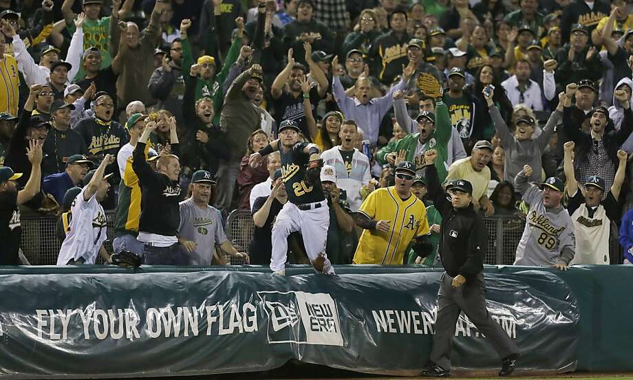 Oakland Athletics third baseman Josh Donaldson (20) looks to throw the ball after catching a foul ball into the seats by Texas Rangers' David Murphy during the sixth inning of a baseball game in Oakland, Calif., Tuesday, Sept. 3, 2013. Third base umpire Phil Cuzzi, right, makes thecall as fans cheer. (AP Photo/Jeff Chiu) Photo: Jeff Chiu, Associated Press