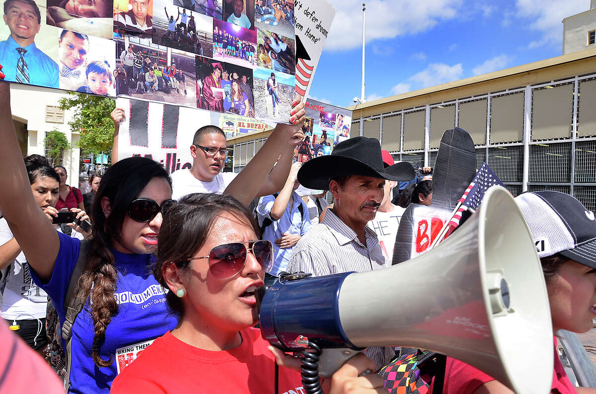 Alicia Torres-Don, from San Antonio, uses a megaphone to lead a group of supporters as they welcome a group of 30
