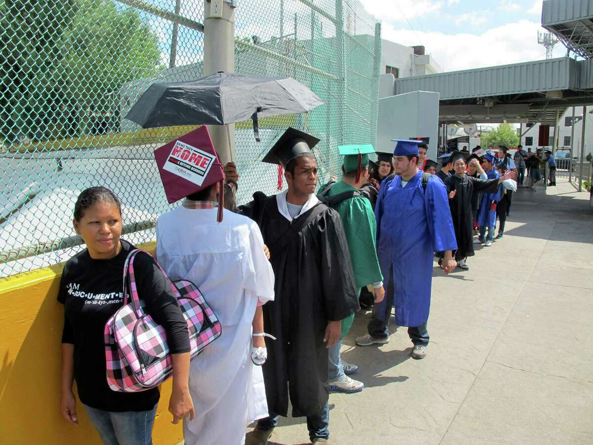 Wearing graduation-style caps and gowns, U.S.-raised immigrants wait on the Mexican side of the international bridge as they try to return to the U.S. from Nuevo Laredo, Mexico, Monday, Sept. 30, 2013. Nearly three dozen migrants marched across the U.S.-Mexico border without papers Monday, the latest group of a younger generation brought to the U.S. illegally as children that seeks to confront head-on immigration policies they consider unjust. (AP Photo/Christopher Sherman)