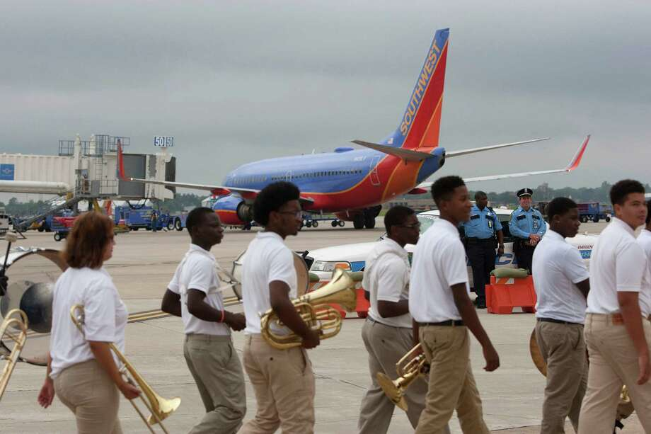Members of the Sterling Aviation Magnet High School band walk past a Southwest airplane after Gary Kelly, CEO, Southwest Airlines, Houston Mayor Annise Parker and city officials broke ground on what will be the new international terminal at William P. Hobby Airport Monday, Sept. 30, 2013, in Houston. 