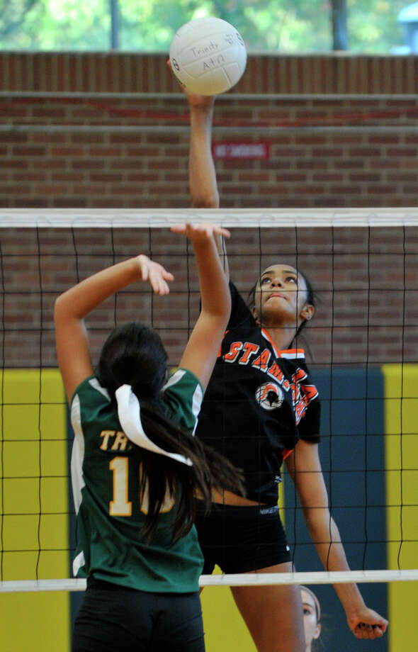 Stamford's Brianna Gordon spikes the ball past Trinity Catholic's Alexis Melfi during their match at Trinity Catholic High School in Stamford, Conn., on Monday, Sept. 30, 2013. Stamford beat Trinity in three sets. Photo: Jason Rearick / Stamford Advocate