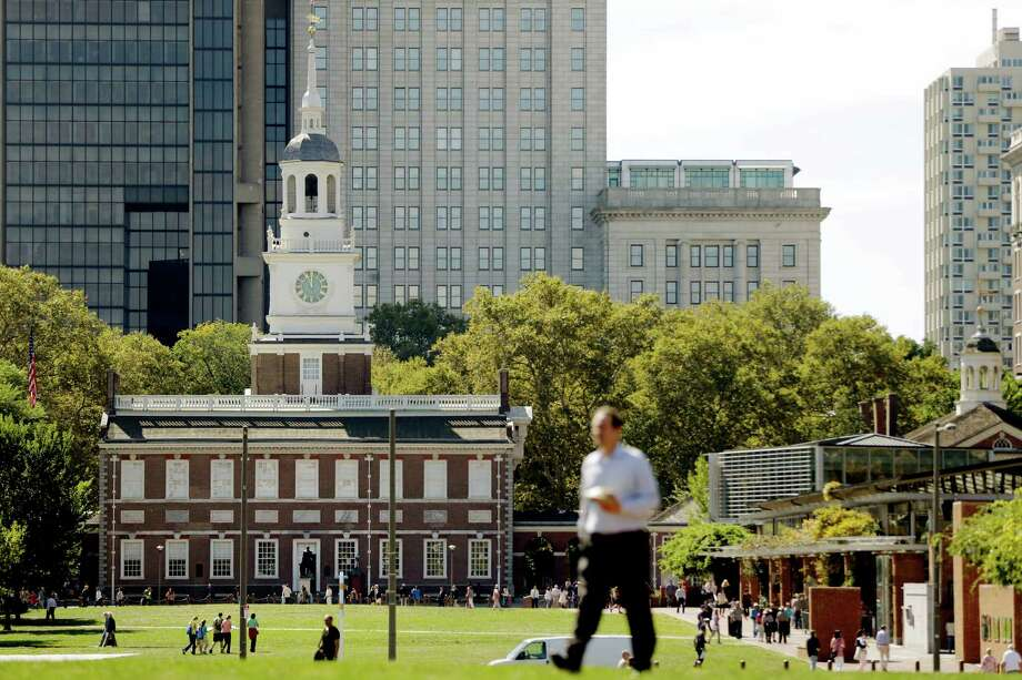 A man walks past Independence Hall at Independence National Historical Park in Philadelphia, Monday, Sept. 30, 2013 as the government teeters on the brink of a partial shutdown at midnight unless Congress can reach an agreement on funding. A conservative challenge to President Barack Obama's cherished health care law pushed the federal government to the brink of a partial shutdown Monday, with the Senate expected to convene just hours before a deadline to pass a temporary spending bill. If no compromise can be reached by midnight, Americans would soon see the impact: National parks would close. Photo: Matt Rourke, Associated Press