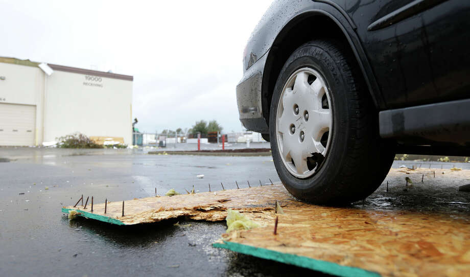 A car is shown with a piece of debris under it at Northwest Door in Puyallup, Wash., Monday, Sept. 30, 2013. The building was damaged when a tornado moved through the area earlier in the day. Photo: Ted S. Warren, Associated Press / Associated Press