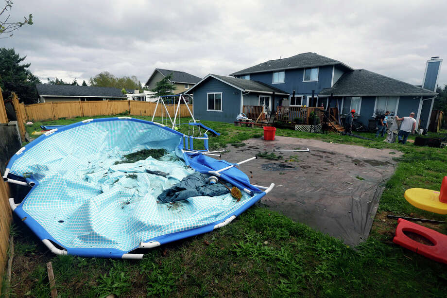 An above-ground pool sits collapsed at the home of Neal O'Connell as O'Connell, right, works to clean up other debris in the Frederickson neighborhood near Puyallup, Wash., Monday, Sept. 30, 2013. A tornado swept through the area earlier in the day, causing damage to several dozen homes. Photo: Ted S. Warren, Associated Press / Associated Press