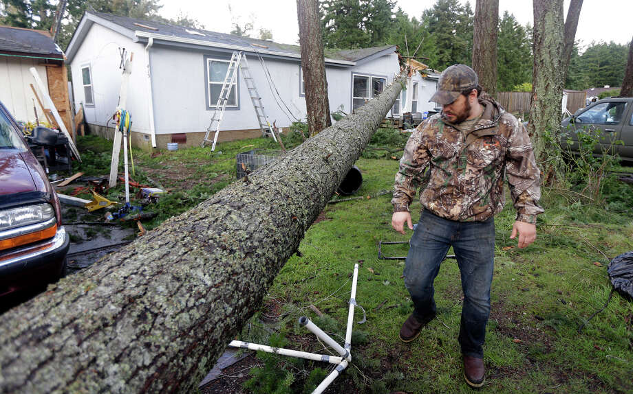 Paxton Hursh looks at a tree that fell on his family's home after a tornado moved through the area earlier in the day in the Frederickson neighborhood near Puyallup, Wash., Monday, Sept. 30, 2013. An early winter storm dumped record amounts of rain and knocked out power for thousands in the Pacific Northwest. Photo: Ted S. Warren, Associated Press / Associated Press