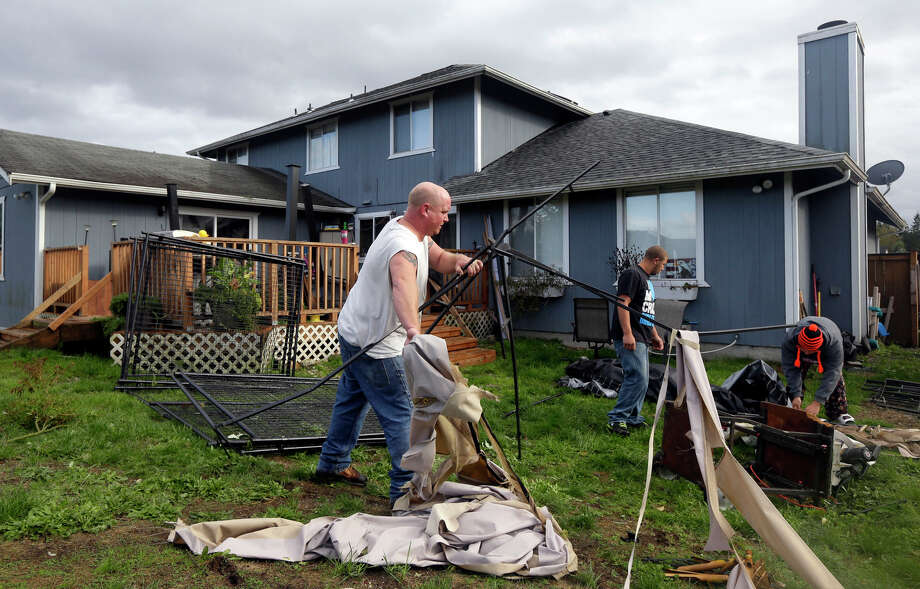 Neal O'Connell, center, works to clean up a covered dog kennel that was blown from his side driveway and into his backyard in the Frederickson neighborhood near Puyallup, Wash., Monday, Sept. 30, 2013. A tornado swept through the area earlier in the day, causing damage to several dozen homes.  Photo: Ted S. Warren, Associated Press / Associated Press