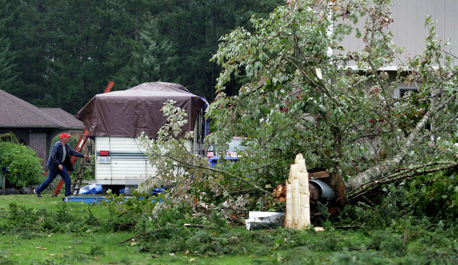 Terry Armstrong, left, secures a tarp on a trailer near a tree that fell down at his home in the Frederickson neighborhood near Puyallup, Wash., Monday, Sept. 30, 2013. A tornado swept through the area earlier in the day, causing damage to several dozen homes. Photo: Ted S. Warren, Associated Press / Associated Press