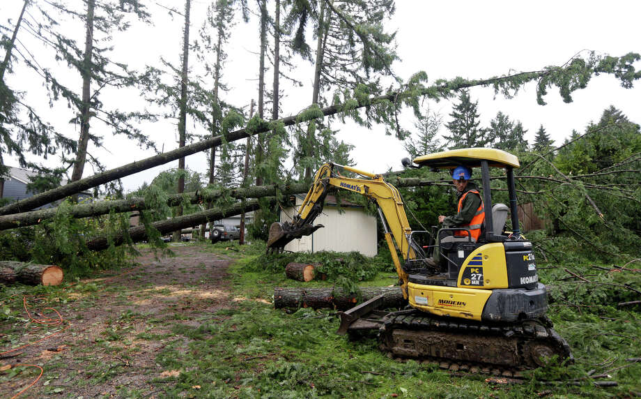 Patrick Broady uses an excavator to clear trees that fell earlier in the day when a tornado moved through the Frederickson neighborhood near Puyallup, Wash., Monday, Sept. 30, 2013. An early winter storm dumped record amounts of rain and knocked out power for thousands in the Pacific Northwest. Photo: Ted S. Warren, Associated Press / Associated Press