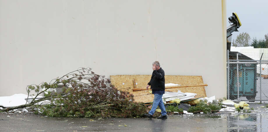 A man walks past a pile of debris at Northwest Door in Puyallup, Wash., Monday, Sept. 30, 2013. The building was damaged when a tornado moved through the area earlier in the day.  Photo: Ted S. Warren, Associated Press / Associated Press