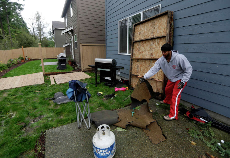 Ralph Jenkins clears debris from his backyard, including roofing materials and a large wooden panel from his neighbor's carport, in the Frederickson neighborhood near Puyallup, Wash., Monday, Sept. 30, 2013. A tornado swept through the area earlier in the day, causing damage to several dozen homes. Photo: Ted S. Warren, Associated Press / Associated Press