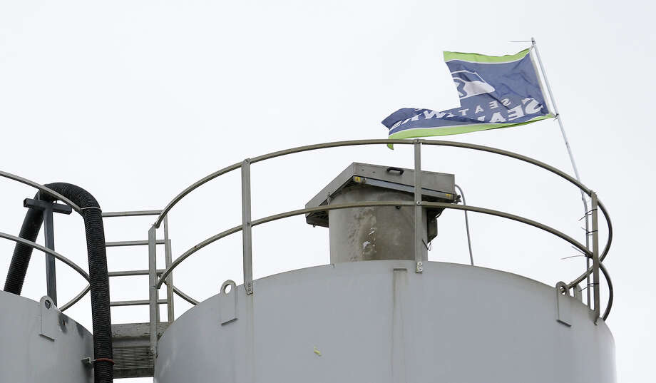A wind-damaged Seattle Seahawks flag flies Monday, Sept. 30, 2013 at EnCon Washington in Puyallup, Wash. The flag was damaged when a tornado moved through the area earlier in the day. EnCon makes engineered concrete products and the building shown is used to build sections for the tunnel currently being dug to replace the Seattle Viaduct. Photo: Ted S. Warren, Associated Press / Associated Press