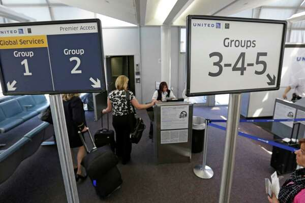 United Airlines passengers board a flight using the Premier Access line at O'Hare International Airport in Chicago. Airlines are selling new extra services and copying marketing methods honed by retailers.