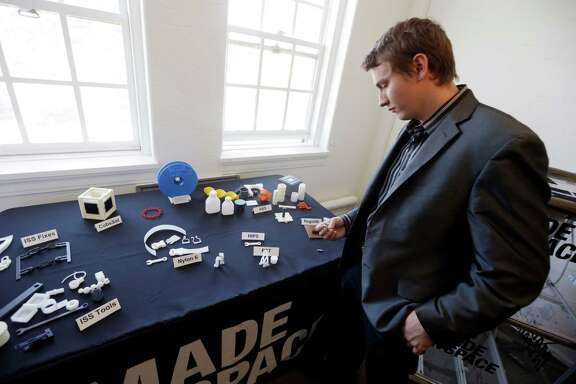 Aaron Kemmer, CEO and co-founder of Made in Space, looks through some items made with the company's 3D printer which will eventually be used in space on Monday, Sept. 16, 2013, in Mountain View, Calif. One of the biggest obstacles to space exploration is that you need to bring everything with you: tools, equipment, spare parts, satellites. NASA is working with a Silicon Valley company to make specialized 3D printers that would allow astronauts to produce the things they need on-demand when they're in space, allowing them to travel farther from the Earth. (AP Photo/Marcio Jose Sanchez)