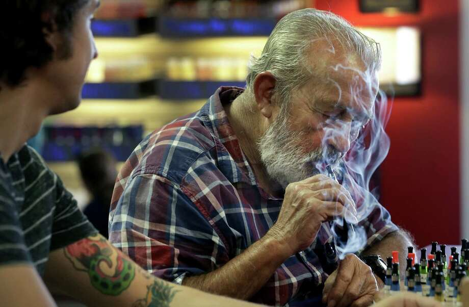 Daniel Lopez, 76, tastes a flavor at the Flavor Wheel at Thanks for Vaping store on Wednesday, Sept. 18, 2013. Lopez, a native of Cuba, grew up smoking the famous cigars and strong cigarettes from his homeland.  He moved to the U.S. when he was 20 years old, during the Cuban Revolution, and has continued smoking cigars.  His son and daughter-in-law, also smokers, are joinging his effort to stop smoking by taking up E-Cigarettes. At left is Banner Matney Assistant Manager of the shop. Photo: BOB OWEN, San Antonio Express-News / © 2012 San Antonio Express-News