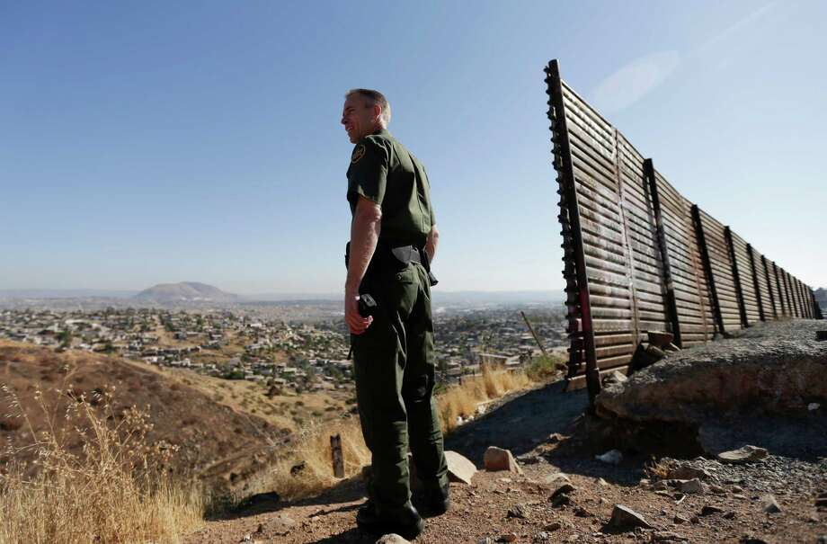 FILE - In this June 13, 2013 file photo, US Border Patrol agent Jerry Conlin looks out over Tijuana, Mexico, behind, along the old border wall along the US - Mexico border, where it ends at the base of a hill in San Diego.  Photo: Gregory Bull, STF / AP