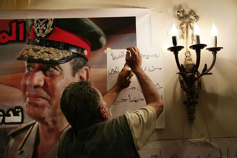 "A supporter of Defense Minister Gen. Abdel-Fattah el-Sissi hangs a poster with Arabic that reads, ""Sissi you are a gift from God, your people are here for you,"" during campaign to collect signatures and nominate el-Sissi to run for Egypt's president at Pyramisa hotel in Cairo, Egypt, Monday, Sept. 30, 2013. A group of professionals, lawyers, and ex-army officers have launched a campaign to collect signatures urging el-Sissi to run for presidency just two months after he ousted former Egyptian President Mohammed Morsi. (AP Photo/Nariman El-Mofty) Photo: Nariman El-Mofty, Associated Press"