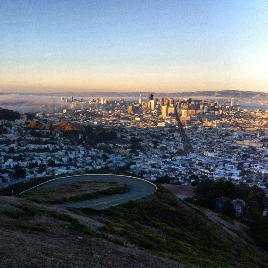 """Jenn Yan, who lives in the  Lakeshore neighborhood, took this breathtaking shot of the view of the city from Twin Peaks, complete with a blanket of fog, which she writes is """"essential to the identity of the city."""""""