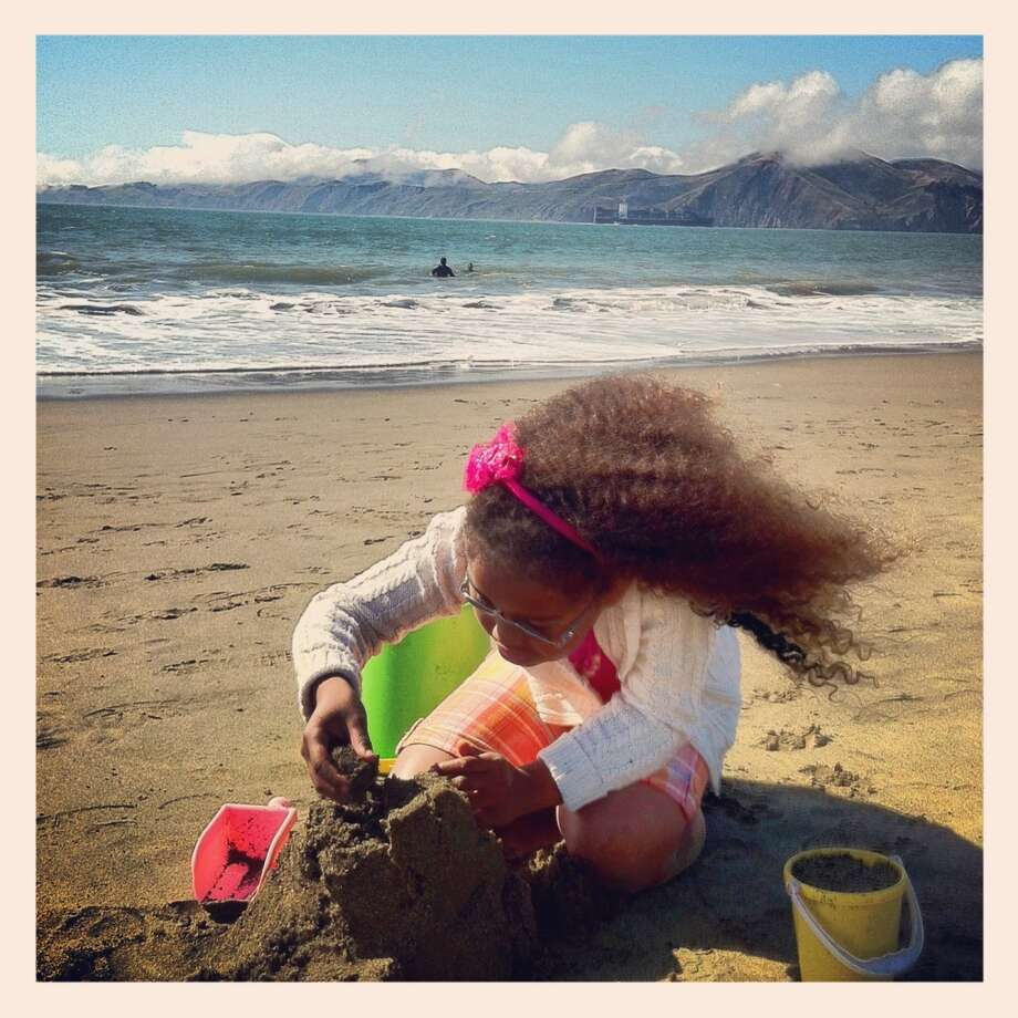 Jessica Jordan Thompson lives in the Presidio National Park with her four children. This photo is of her youngest daughter making her sand castle creation at Baker Beach.