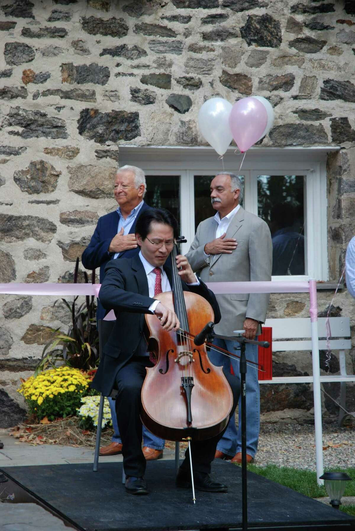 Kenneth Kuo, owner of Rental Instrument, LLC, plays the National Anthem at the establishment's grand opening Sunday as Norwalk Mayor Richard Moccia and superintendent of schools Manny Rivera look on.