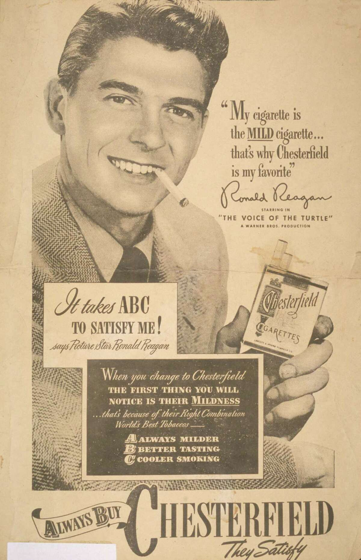 Movie actor and future President Ronald Reagan holds a pack of cigarettes and smokes as he appears in a print advertisement for the Chesterfield brand of cigarettes, late 1940s. Text includes: 'My cigarette is the mild cigarette...that's why Chesterfield is my favorite' and 'It takes ABC to satisfy me! says picture star Ronald Reagan.'