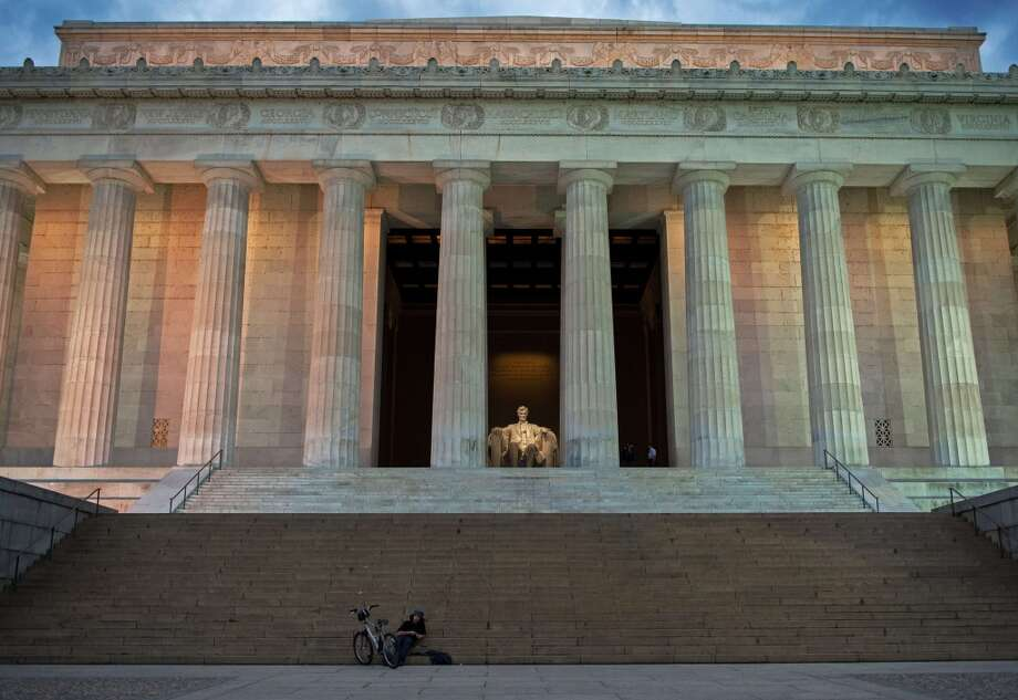 A man rests in front of the Lincoln Memorial on the National Mall in Washington, DC, on October 1, 2013. The United States lurched into a dreaded government shutdown today for the first time in 17 years, after Congress failed to end a bitter budget row after hours of dizzying brinkmanship. Photo: PAUL J. RICHARDS, AFP/Getty Images