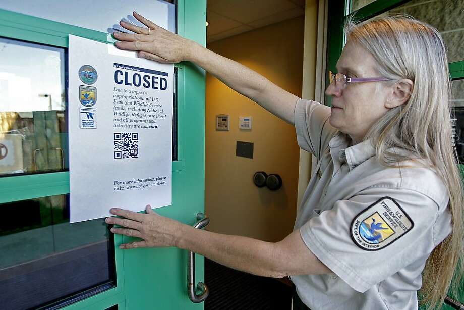 "Jeanne Holler, Deputy Refuge Manager at the Minnesota Valley Wildlife Center, hangs a ""Closed"" signs outside the center in Bloomington, Minn., early Tuesday, Oct. 1, 2013. All of Minnesota's national parks and other national recreational sites will be closed due to the government shut down. Photo: Elizabeth Flores, Associated Press"