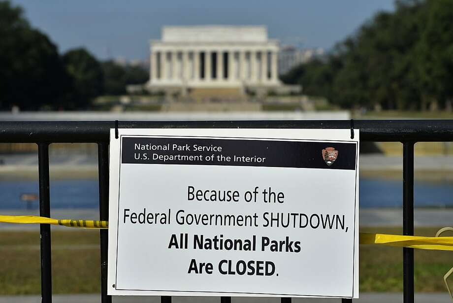 A closure sign is seen at the World War II memorial (with the Lincoln memorial in the distance) in Washington, DC, on October 1, 2013. The US government shut down Tuesday for the first time in 17 years after a gridlocked Congress failed to reach a federal budget deal amid bitter brinkmanship. Some 800,000 federal workers have been furloughed in a move reminiscent of two previous shutdowns -- for six days in November 1995 and 21 days from December that year into early 1996. Photo: Jewel Samad, AFP/Getty Images