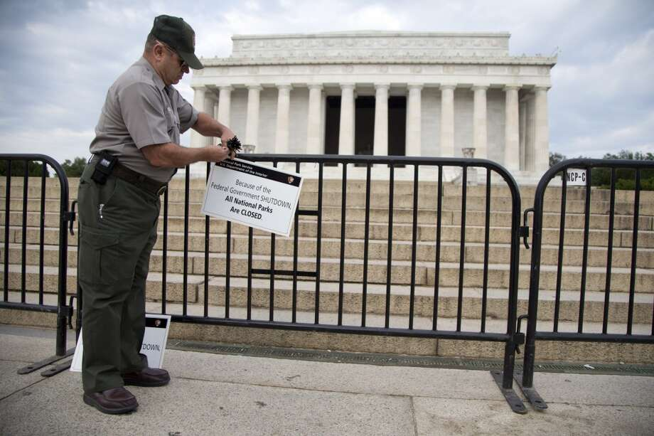 A National Park Service employee posts a sign on a barricade to close access to the Lincoln Memorial in Washington, Tuesday, Oct. 1, 2013. Photo: Carolyn Kaster, Associated Press