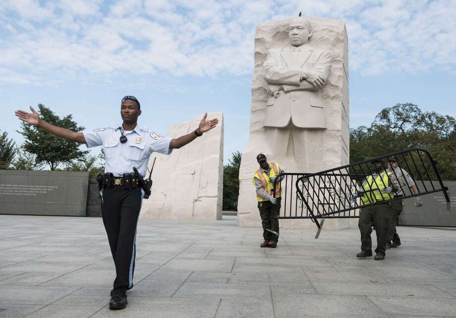 A US Park Police Officer and National Park Service employees close the Martin Luther King Jr. Memorial on the National Mall October 1, 2013 in Washington, DC. Photo: BRENDAN SMIALOWSKI, AFP/Getty Images