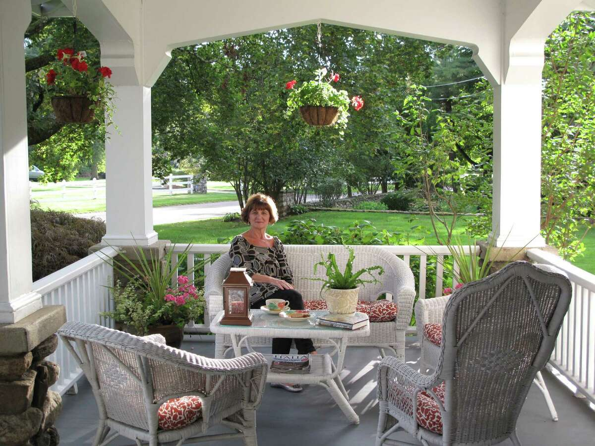 Josephine Weston enjoys tea and biscuits on her front porch. Josephine and her husband, Stephen, say the porch 21 Old Studio Road was the reason they bought the house. Sept. 26, 2013. New Canaan, Conn.