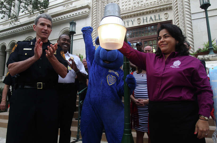 San Antonio Distict 3 City Council woman Rebecca Viagran (right) turns on a symbolic street light Tuesday October 1, 2013 in front of City Hall along with San Antonio Police Chief William McManus (left) and San Antonio Fire Chief Charles Hood and the mascot Blue Bear (center) in recognition of this year's National Night Out. From 6 to 10:00 p.m. San Antonio and other area neighborhoods will host a variety of special events to include block parties, cookouts, parades, visits from police, flashlight walks and more. Photo: JOHN DAVENPORT, SAN ANTONIO EXPRESS-NEWS / ©San Antonio Express-News/Photo may be sold to the public