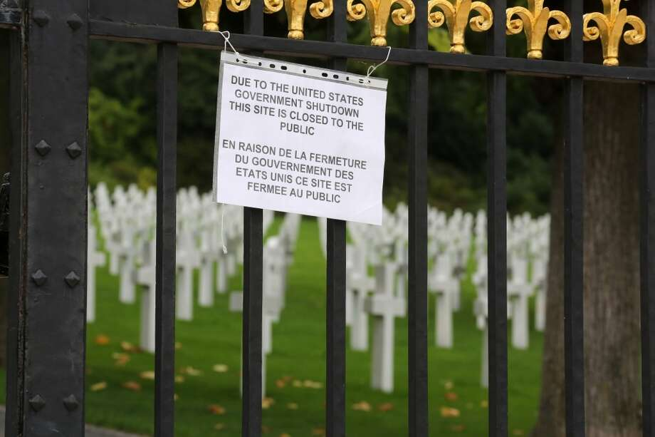 A notice advising visitors that the American Cemetery is closed due to the partial shutdown of the U.S. federal government hangs from the gates of the cemetery in Suresnes, west of Paris. Photo: Remy De La Mauviniere, Associated Press