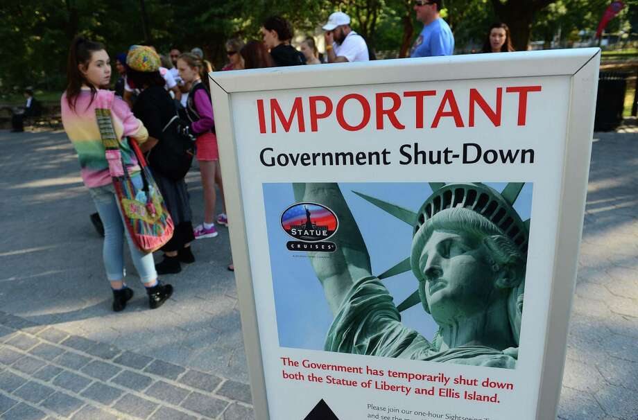 TOPSHOTS Tourists walk by a sign announcing that the Statue of Liberty is closed due to a US government shutdown in New York, October 1, 2013. Government institutions and national parks around the US were closed and thousands of employees were furloughed after Congress was unable to agree on a federal budget and shut down the goverment for the first time in 17 years. AFP PHOTO/Emmanuel DunandEMMANUEL DUNAND/AFP/Getty Images Photo: EMMANUEL DUNAND, AFP/Getty Images / AFP