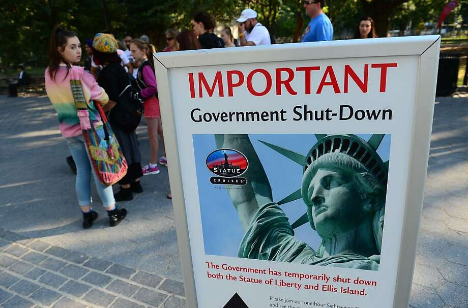 Tourists walk by a sign announcing that the Statue of Liberty is closed due to a US government shutdown in New York, October 1, 2013. Government institutions and national parks around the US were closed and thousands of employees were furloughed after Congress was unable to agree on a federal budget and shut down the goverment for the first time in 17 years. Photo: Emmanuel Dunand, AFP/Getty Images