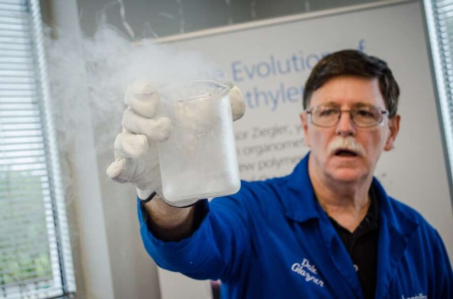 Dale Glazner with a beaker of liquid nitrogen, shows off some of the small-scale experiments LyondellBasell does as part of its educational initiatives. Photo: Jamaal Ellis, For The Chronicle