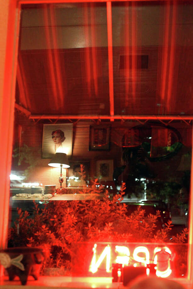 The neon open sign reflects in a dining room window on the last night of Liberty Bar in 2010. Photo: Jennifer Whitney, Special To The Express-News / spoecial to the San Antonio Express-News