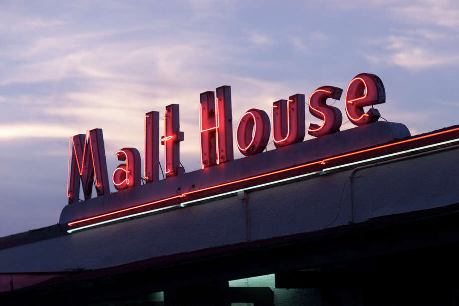 Neon lights of the Malt House sign glow as the daylight fades on another day. Photo: Kin Man Hui