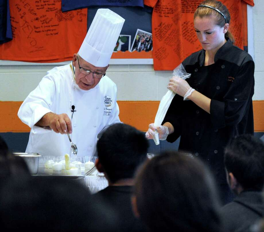 Chef Paul Prosperi, of the Culinary Institute of America, is assisted by Karyssa Miguel, 17, a senior at Danbury High School, Tuesday, Oct. 1, 2013. They are making tiramisu. Photo: Carol Kaliff / The News-Times