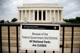 """A sign reading """"Because of the Federal Government SHUTDOWN All National Parks are Closed"""" is posted on a barricade in front of the Lincoln Memorial in Washington, Tuesday, Oct. 1, 2013. Congress plunged the nation into a partial government shutdown Tuesday as a long-running dispute over President Barack Obama's health care law stalled a temporary funding bill, forcing about 800,000 federal workers off the job and suspending most non-essential federal programs and services."""