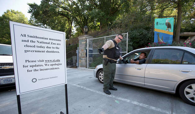 National Zoological Park Police Officer Will Jones halts Miguel Miranda and his family, visiting from Mexico, at the entrance of the Smithsonian National Zoological Park in Washington. Photo: Manuel Balce Ceneta, ASSOCIATED PRESS / AP2013