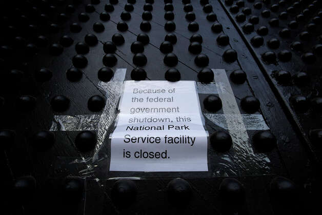 """A sign posted on a door at New York's Castle Clinton National Monument reads, """"Because of the federal government shutdown, this National Park Service facility is closed."""" Photo: MARK LENNIHAN, AP / AP"""